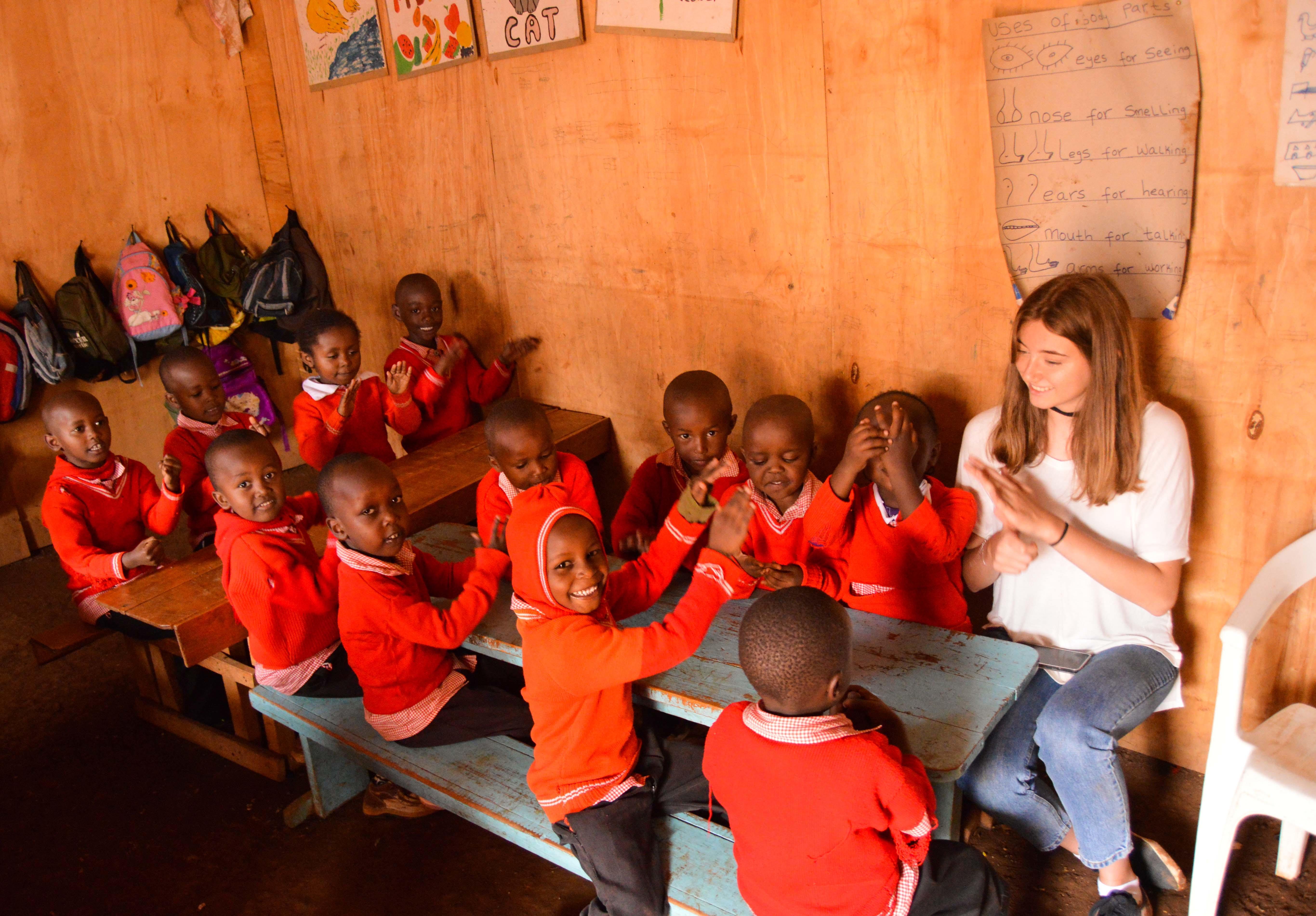 Adolescente le enseña canciones a niños de un preescolar durante su programa de voluntariado para jóvenes en Kenia.